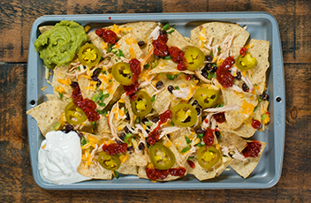 Jeff's Mexican Nachos: Combine rotisserie chicken with beans, cheese and Jeff's Tamed Sliced Jalapeños for a quick game day appetizer or week night dinner for two.