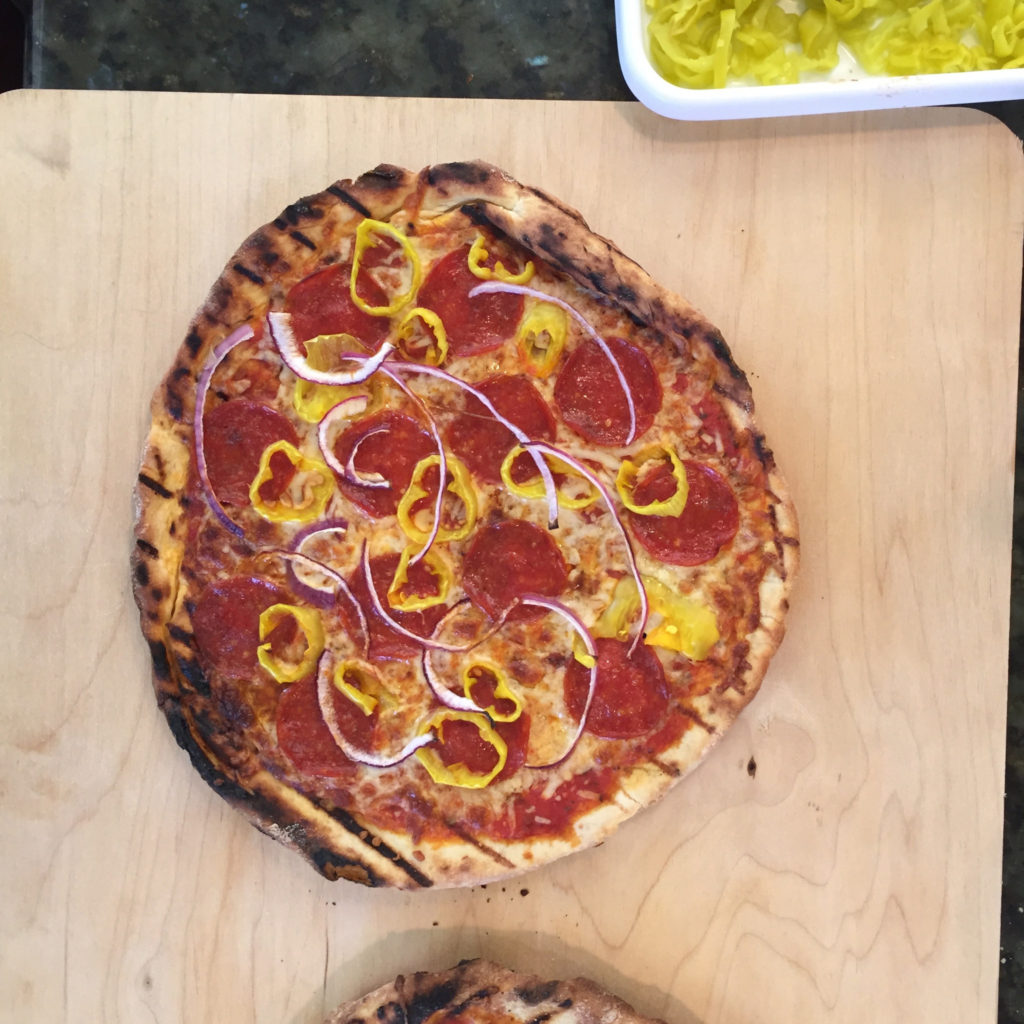Grilled pizza topped with Sliced Golden Greek Peperoncini, light cheese and thinly sliced red onions.